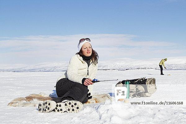 Young woman ice fishing