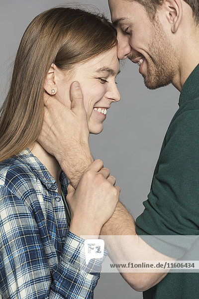 Seitenansicht des glücklichen romantischen Paares vor grauem Hintergrund