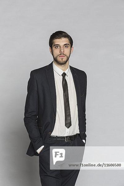 Porträt eines selbstbewussten Geschäftsmannes mit Händen in den Taschen vor grauem Hintergrund