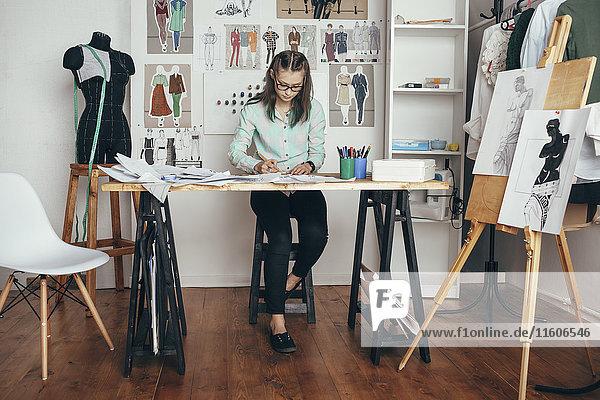 Schöne Designerin  die an der Werkbank im Studio arbeitet.
