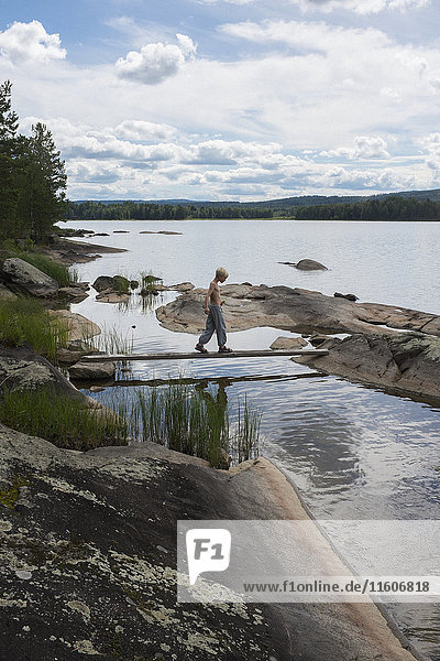 Boy walking on log bridge