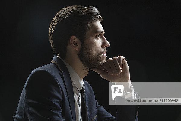 Seitenansicht des nachdenklichen Geschäftsmannes mit Hand auf Kinn vor schwarzem Hintergrund