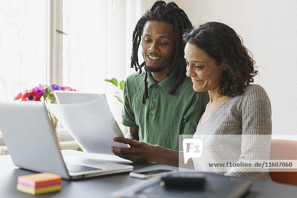 Paar Lesung von Dokumenten im Sitzen mit Laptop am Tisch