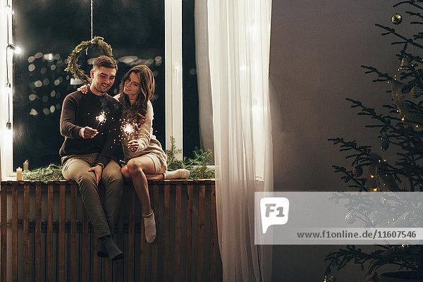 Ein glückliches Paar spielt mit Wunderkerzen  während es zu Weihnachten auf dem Fensterbrett sitzt.