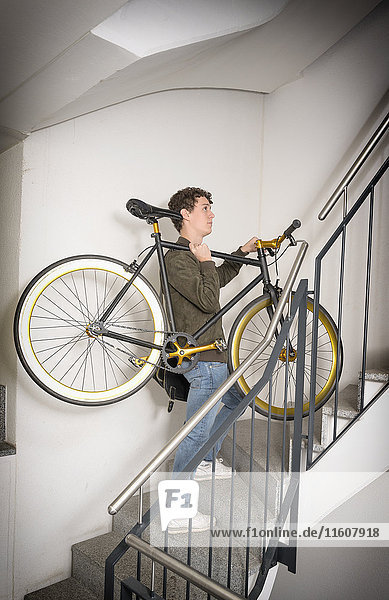 Young man carrying fixie bicycle up stairs Hipster