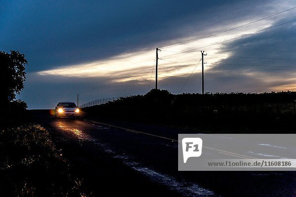 A lone car with its headlights on driving on a 2 lane road at dusk in Texas.