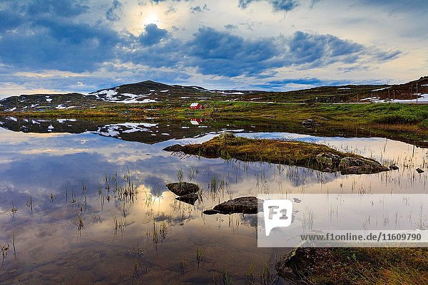 Lonely hut on the berder of a small pond in Handargervidda national park  hordaland  norway.