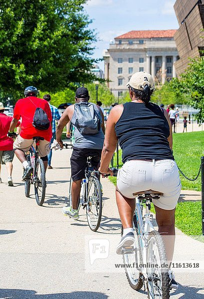 Tourists in shorts  lined up behind each other riding Bikes in Washington DC.