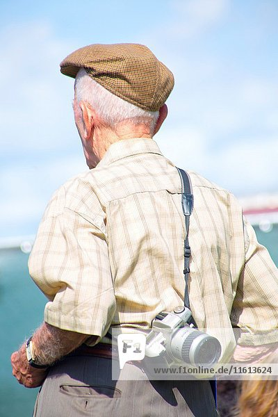 Older caucasian man with a beret in his 60's 70's 80's walking on the street with his old fashion camera on his back on a blue sky and sunny day.