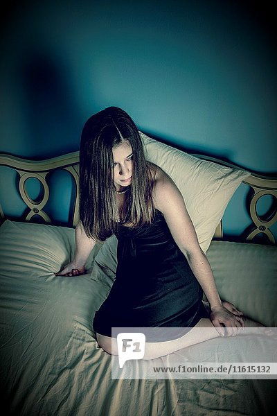 Young woman  wearing a black dress  sitting on her bed.