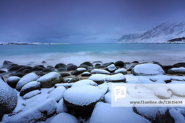 Snow covered rocks on the beach modeled by the wind surround the icy sea Pollen Vareid Flakstad Lofoten Islands Norway Europe.