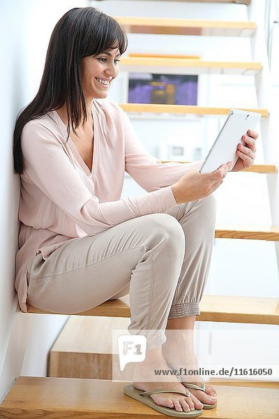 Woman sitting on stairs and using digital tablet