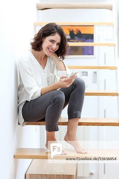 Woman sitting on stairs and using smart phone