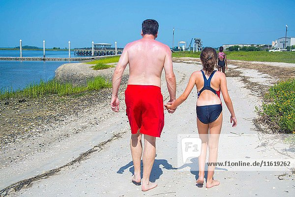 A caucasian male in his 40's with sunburns all over his back  wearing red shorts bathing suit  in the middle of the summer holding hands to his daughter on the sandy beach.