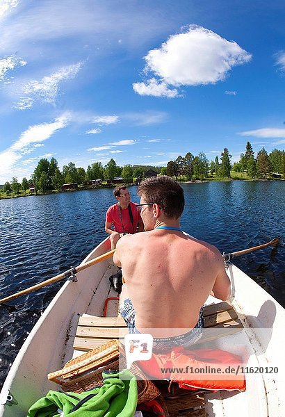 Brothers rowing a boat  countryside of northern Sweden.