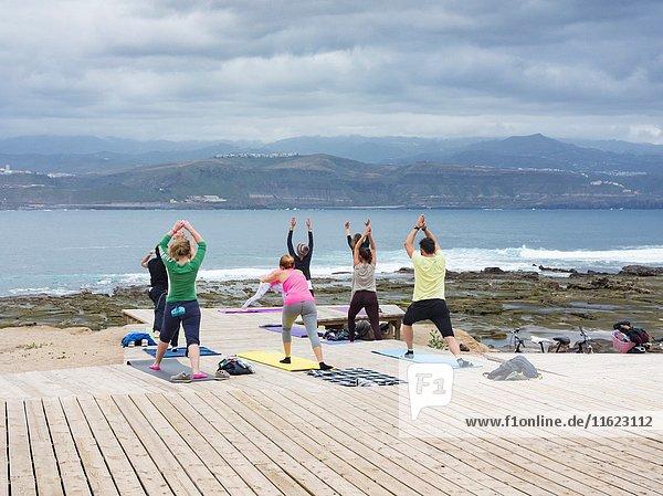 Yoga class overlooking Atlantic Ocean at El Confital near Las Canteras in Las Palmas  Gran Canaria  Canary Islands  Spain.