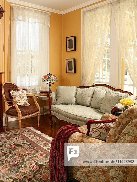 Yellow sitting room with upholstered sofa and floral patterned rug.