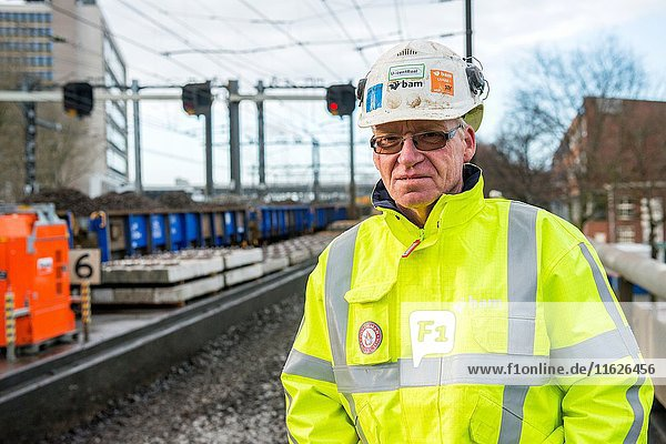 Rotterdam  Netherlands. Senior adult construction worker overseeing the removal of old and used before gravel from a train track in the Willemspoortunnel  during a overhauling job by a ProRail subcontractor.