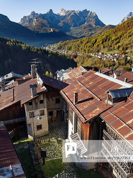 View towards the Tamer mountain range in the dolomites. Village Fornsesighe  an example of the local and original alpine architecture of the Veneto in the dolomites  an UNESCO world heritage. Europe  Central Europe  Italy  October.