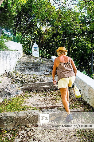 Senior retirred caucasian woman in her 60's  70's doing the road of christ in Martinique.