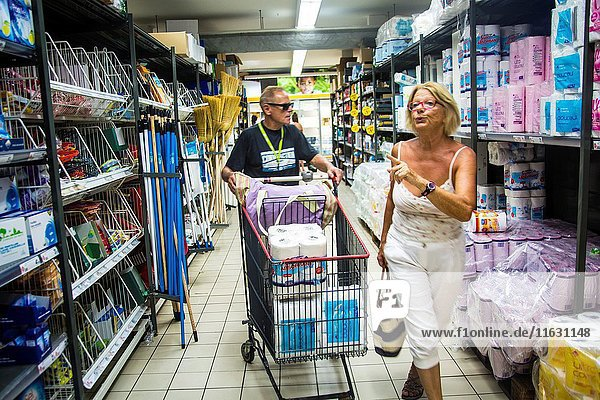 Mature retired senor caucasian woman doing her grocery shopping on vacation.