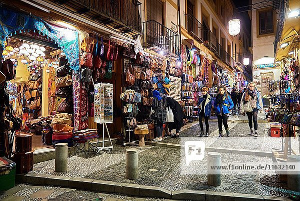 Tourists and souvenir shops selling Moroccan handicrafts at night  Granada  Andalusia  Spain  Europe.