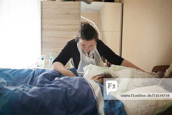 Reportage on a home health care service in Savoie  France. An auxiliary nurse cares for a patient at the end of his life.