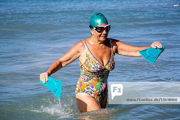 Senior retired caucasian woman  in her 70's  with her swim cap  flippers and goggles  going to the ocean doing her exercices to stay fit.