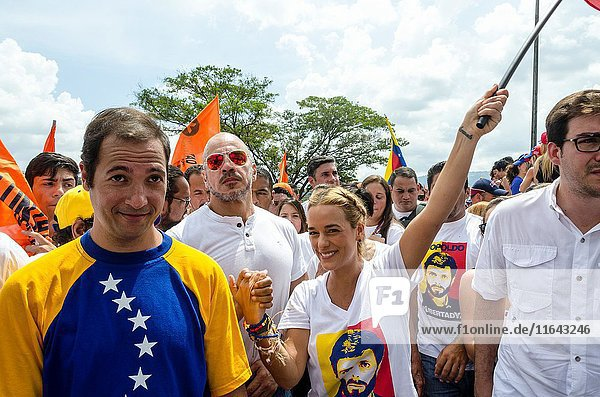 Lilian Tintori (center)  wife of prominent jailed opposition leader Leopoldo Lopez  holds a Venezuelan national flags as she marches against the government of President Nicolas Maduro in the streets of Caracas.