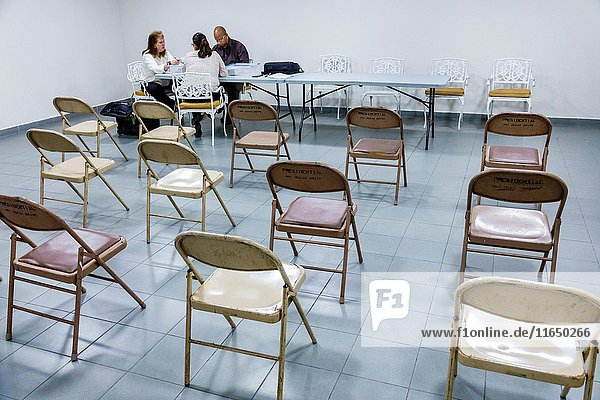 Florida  Miami Beach  condominium board  meeting  table  Black  Hispanic  man  woman  counting ballots  papers  folding chairs  empty  annual election  votes