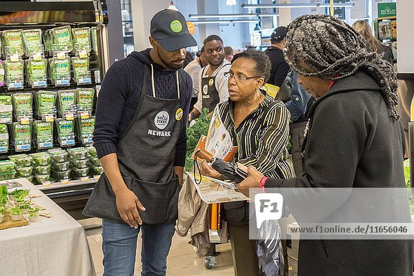 A worker assists a shopper in the new Whole Foods Market in Newark  NJ on opening day. The store is the chain's 17th store to open in New Jersey. The 29  000 square foot store located in the redeveloped former Hahne & Co. department store building is seen as a harbinger of the revitalization of Newark which never fully recovered from the riots in the 1960's.