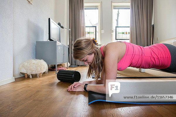 Tilburg  Netherlands. Young adult girly woman working out inside her living room.