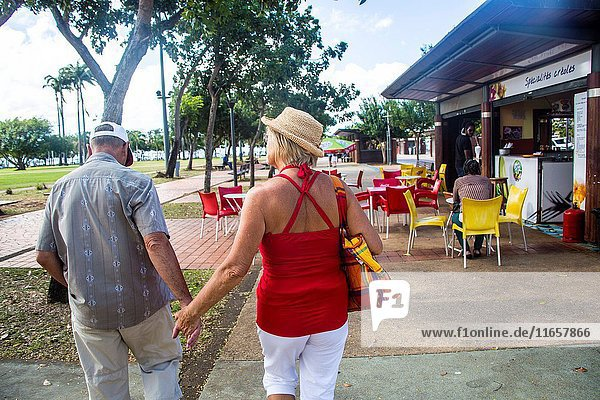 Older mature retired caucasian couple holding hands in the streets of Fort de France on a vacation. He wears a baseball hat and she a straw hat.