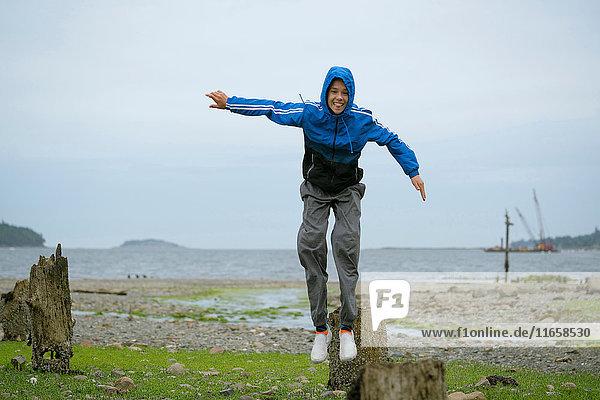 Teenager  der vom Baumstumpf springt  Pacific Rim National Park  Vancouver Island  Kanada
