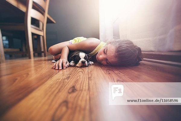 Girl lying on floor with sleeping Boston Terrier puppy