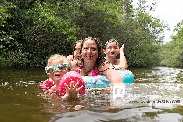 Mutter und Kinder mit aufblasbarem Ring im See  Niceville  Florida  USA