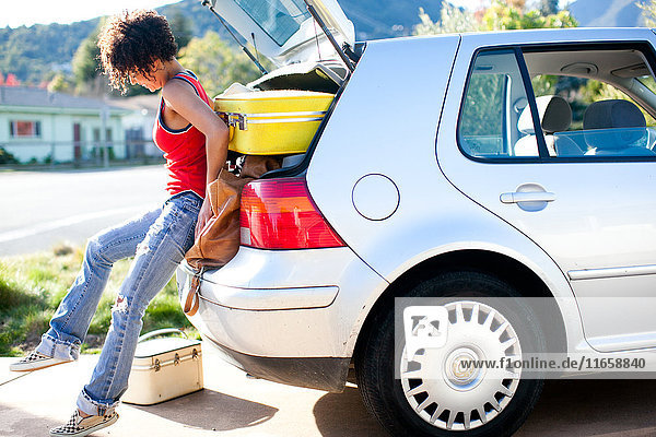 Woman struggling to push luggage into car boot