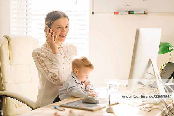 Mutter arbeitet und kümmert sich zu Hause um ihr Baby