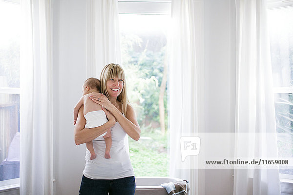 Mid adult woman carrying baby son in living room