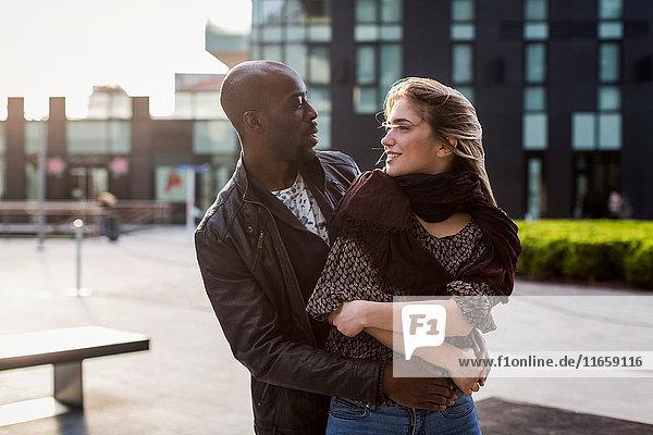 Junges Paar in der Stadt  das sich umarmt und anstarrt.