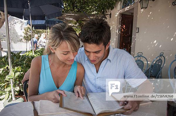 Couple looking at menu at outdoor restaurant  Lake Maggiore  Italy