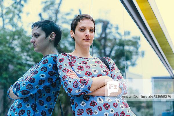Porträt einer an ein Spiegelfenster gelehnten Frau  die Arme verschränkt