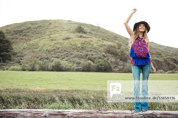Junge Frau im Boho-Stil winkt vom Baumstamm