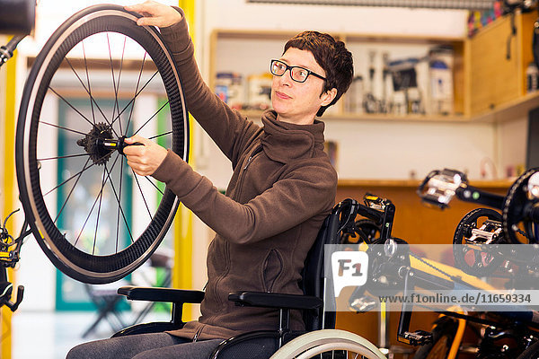 Woman in wheelchair in bicycle repair shop  holding bicycle wheel
