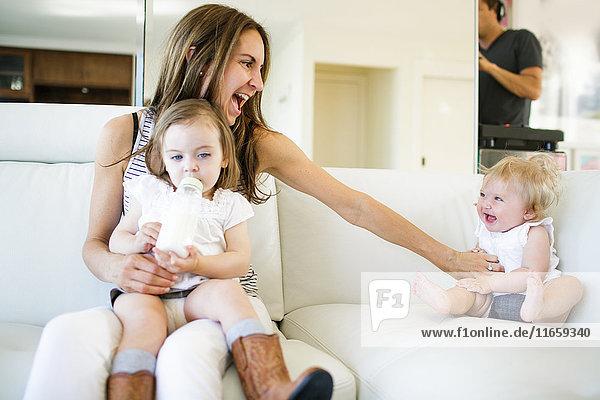 Weibliches Kleinkind auf dem Schoss der Mutter trinkt aus der Babyflasche