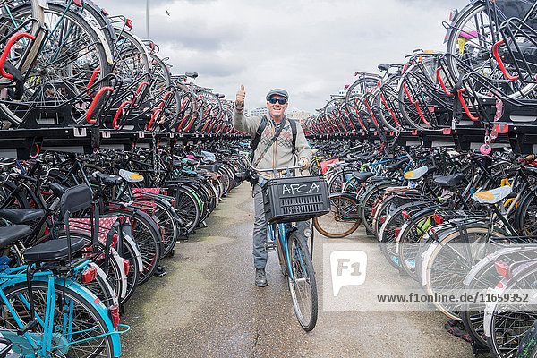 Cyclist on bicycle looking at camera giving thumbs up  Amsterdam  Netherlands