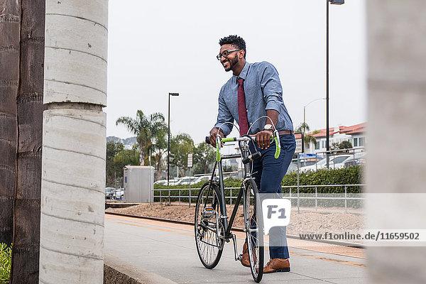 Junger Geschäftsmann Radfahrer auf Bahnsteig