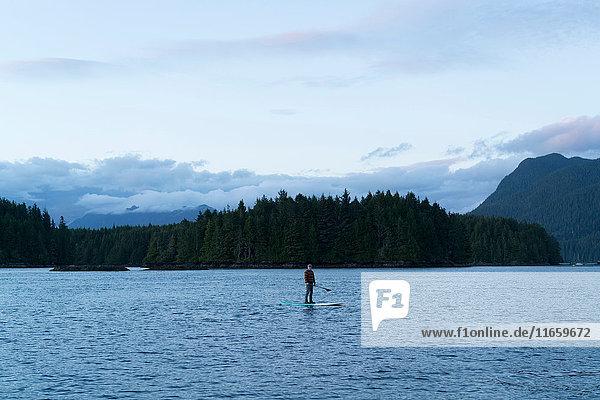 Mann auf einem Paddelbrett auf dem Wasser stehend  Pacific Rim National Park  Vancouver Island  Kanada