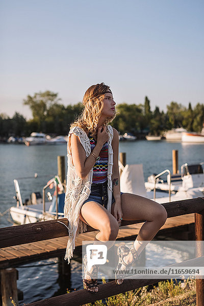Woman sitting on fence by harbour looking away