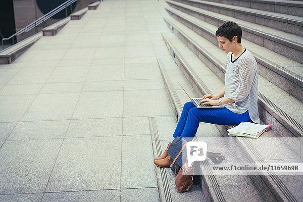 Mittlere erwachsene Frau  die auf Stufen sitzt und einen Laptop benutzt